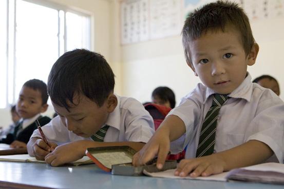 Bambini sui banchi di scuola in una scuola elementare del Nepal.