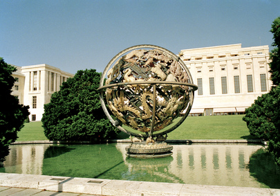 External view of the Palace of Nations in Geneva. A globe stands in front of the Palace, the work of sculptor Paul Manship, a metal sphere, the inside of which contains figures representing the zodiac weaved with one another.
