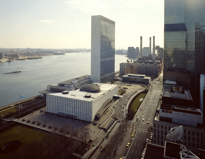 Aerial view of the United Nations Headquarters. Two low rectangular buildings and a skyscraper, overlooking the Hudson River in New York.