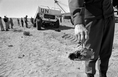 Incidente in un campo minato: in primo piano una mano che sorregge una scarpa dilaniata e sullo sfondo il veicolo dell'ONU coinvolto.