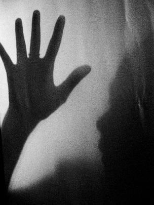 Manifesto sulla violenza di genere presentato a Timor-Est. Immagine in bianco e nero dell'ombra di una mano e del profilo sfumato di una persona.