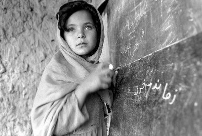 Foto in bianco e nero di una bambina ritratta in piedi di fronte alla lavagna di una scuola dell'UNICEF.