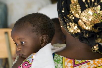 Una donna tiene in braccio un bambino all'interno di un centro di accoglienza per vittime di stupro e violenze durante il genocidio in Rwanda.