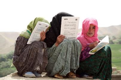 Tre bambine afghane con i capelli coperti da veli colorati studiano, accovacciate a terra.