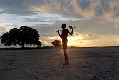 Foto in controluce di un giovane dalla figura esile che tiene sulle spalle un bastone, in un campo di Bahr El Ghazal, Sudan.