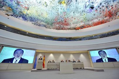 Sala conferenze del Consiglio diritti umani a Ginevra. Vista del tavolo dei relatori e degli schermi mentre trasmettono l'immagine di Ban Ki-Moon, Segretario delle Nazioni Unite.