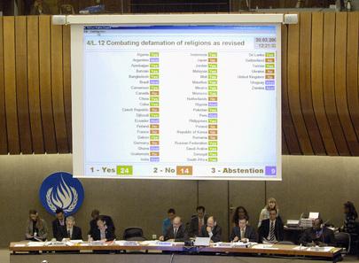 Foto che riprende il tavolo dei relatori e nello sfondo il tabellone elettronico con i risultati di una votazione al Consiglio diritti umani.