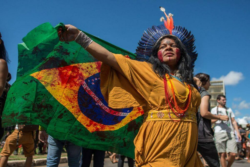 indigenous woman holds brazilian flag with red stains representing blood.