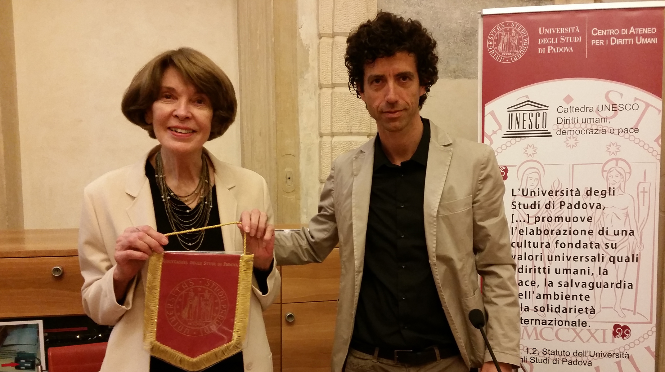 Professor  Roberto De Vogli giving the pennant of the University of Padua to Susan George