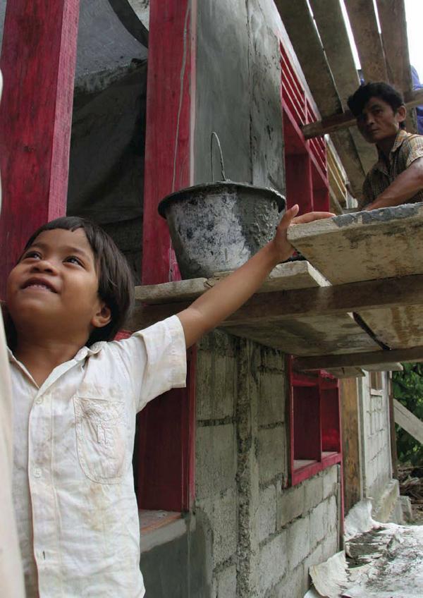 Copertina del Rapporto annuale 2008 di UN-HABITAT, programma delle Nazioni Unite per gli insediamenti umani. Nella foto un bambino sorridente in primo piano ed alle sue spalle un uomo che lavora su una impalcatura di un cantiere edile.