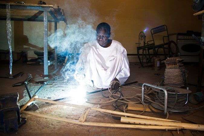 Persona con disabilità del Nord Darfur con una mutilazione alle gambe che costruisce una stampella in un laboratorio di una organizzazione locale.