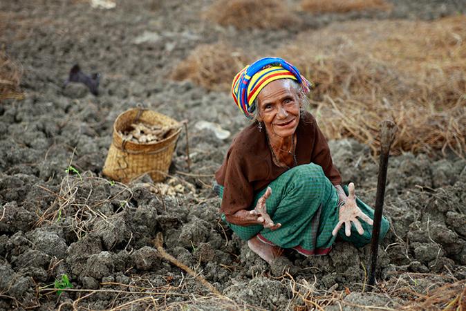 Una donna siede in mezzo ad un campo di terra brulla con il palmo delle mani rivolto verso l'osservatore