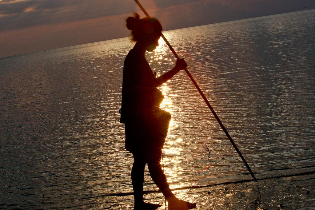 Una donna pesca del pesce al tramonto nel Distretto di Dili.