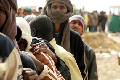 Migliaia di rifugiati, prevalentemente dal Bangladesh, Nigeria, Mali e Ciad, attendono la distribuzione di cibo nella città di confine di Sallum, in Egitto, dopo la fuga dalla Libia.