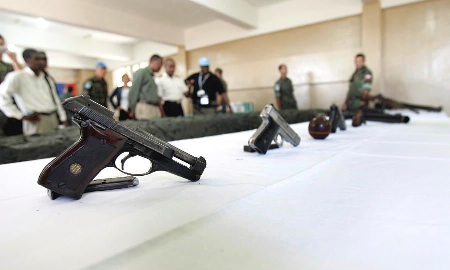 Su un tavolo alcune delle dieci armi consegnate volontariamente da alcuni membri di una gang di Port-Au-Prince, Haiti.