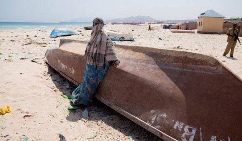 Una donna etiope in piedi accanto ad una barca abbandonata sulla spiaggia a Bossaso, uno dei porti più grandi della Somalia, 2011