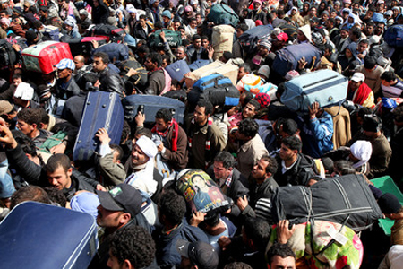 Thousands of people with packanges and bags try to leave Libya at the Tunisian border