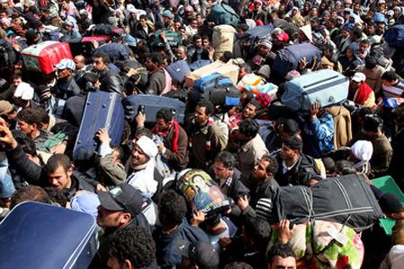Migliaia di persone con pacchi e valigie tentano di lasciare la Libia al confine con la Tunisia