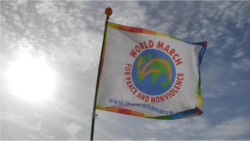Una bandiera con il logo della Marcia Mondiale per la Pace e la Nonviolenza