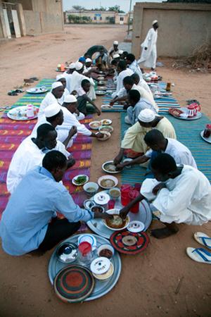 Celebrazione del Ramadan nel villaggio di El Fashir, Nord Darfur. Un gruppo di persone siede attorno ad una stuoia dove sono posti piatti e vivande.
