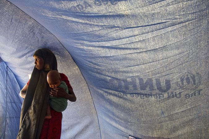 Una donna somala rifugiata con suo figlio in piedi all'interno di una tenda di un campo profughi dell'UNHCR, Etiopia, 2011
