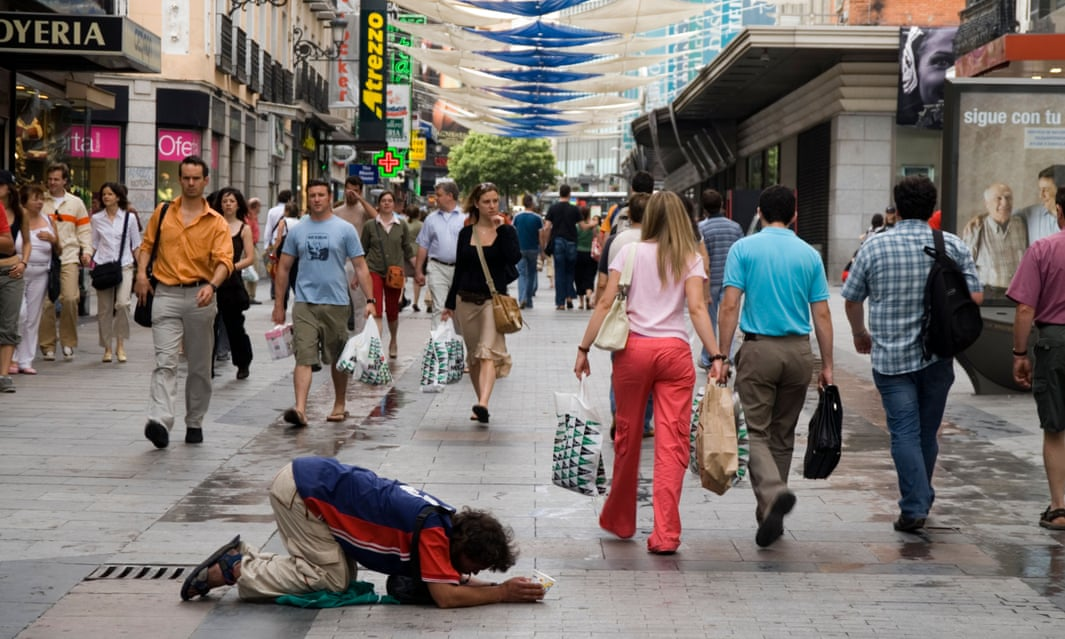 Un uomo che chiede l'elemosina in Calle de Preciados a Madrid.