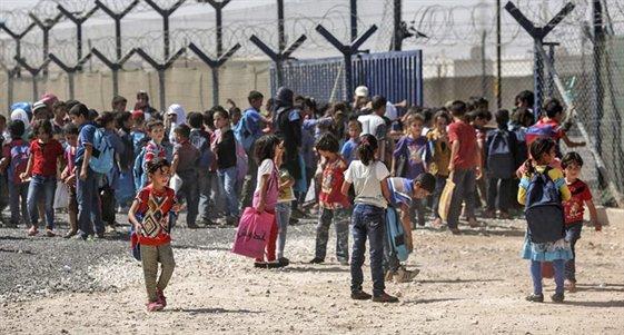 Bambini siriani si riuniscono fuori dalla scuola del campo rifugiati Za'atari in Giordania, Settembre 2015.