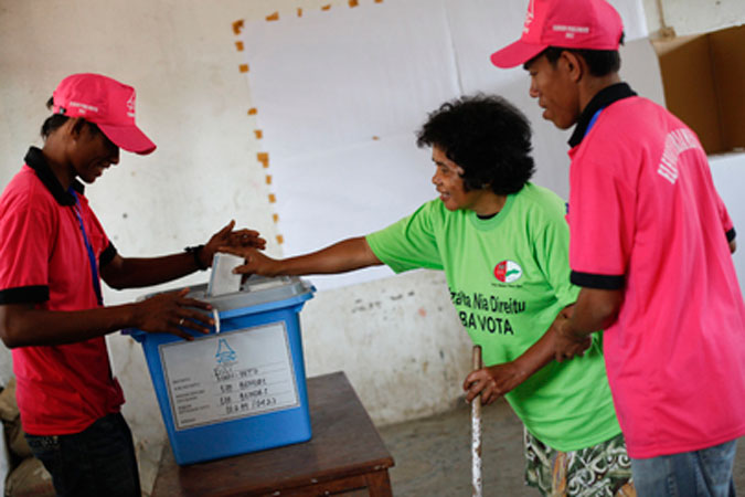 Two Polling officers aid a voter cast her ballot in Timore-Leste's parliamentary elections