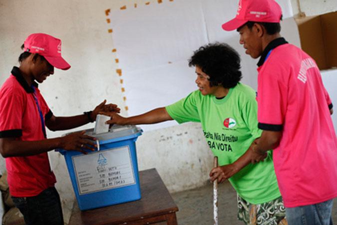 Due scrutatori aiutano un'elettrice ad inserire la propria scheda nell'urna durante le elezioni parlamentari a Timor Est