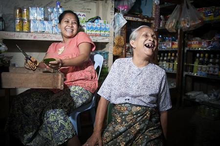 Una donna di settant'anni ride insieme con un altro membro della famiglia dentro un negozio a Tachilek, Myanmar