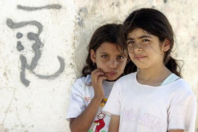 Due bambine registrate dall'Agenzia delle Nazioni Unite per il Soccorso e l'Occupazione (UNRWA) posano nel campo profughi di Acqba Jaber, nelle vicinanze di Jericho, accanto ad un muro con graffiti in arabo.