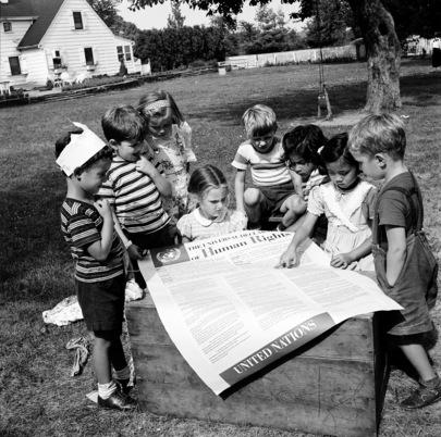 Foto in bianco e nero di un gruppo di bambini mentre leggono il poster con la Dichiarazione universale dei diritti umani, 1950.