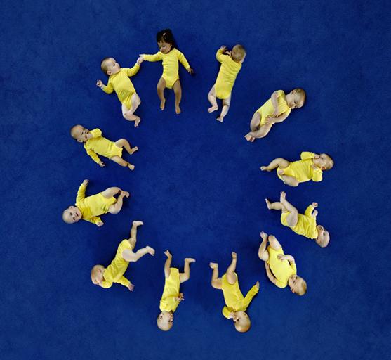 sfondo blu, neonati vestiti di giallo disposti in cerchio