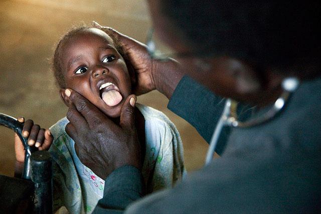 Foto di bambino esaminato dal dottore al fine di valutare se è in grado di viaggiare, Campo per sfollati Kalma di Nyala (Darfur)