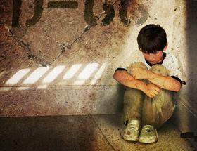 Un bambino accovacciato in una stanza vuota guarda per terra