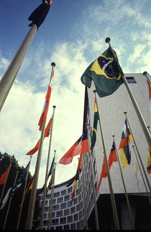 Photo displaying the flags of some member states standing tall in front of the facade of UNESCO Headquarters.