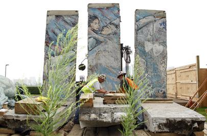 Operai lavorano su alcuni resti del muro di Berlino per la lororicollocazione nel 2008