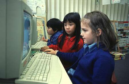 Due bambine di fronte allo schermo di un computer.