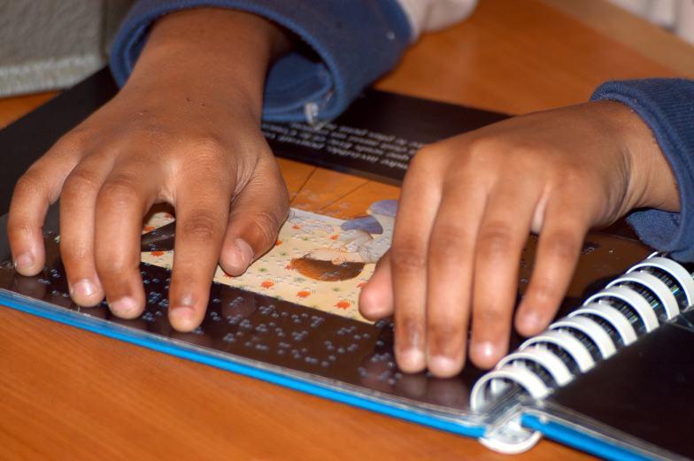 In prinmo piano due mani di un bambino mentre leggono con l'ausilio di una tavoletta tattile un testo in Braille.