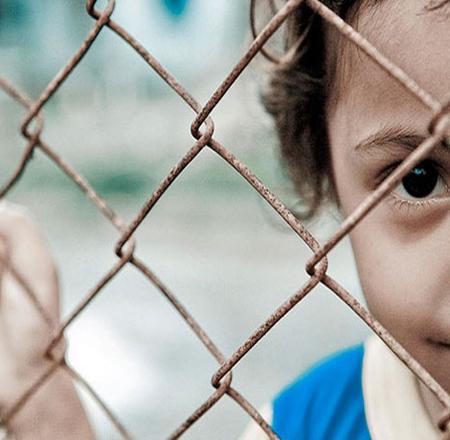foto di bambina dietro una rete metallica