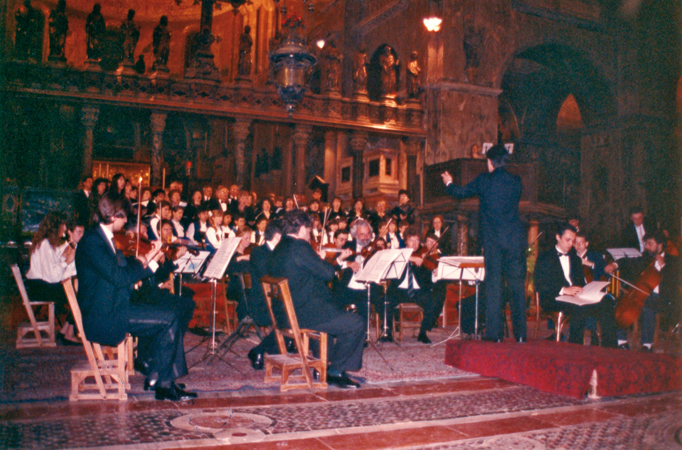 "Photo taken at the concert: ""Musiche per una professione di pace,"" or Music for a Profession of Peace. Venice, St. Mark's Basilica, 23 May 1991. In the photo one can observe the conductor directing the orchestra."