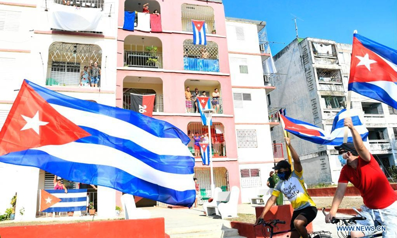 People holding cuban flags. On the background, flags hanging from the balconies.