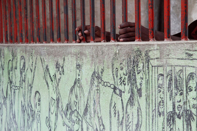 Un prigioniero afferra le sbarre di un muro esterno al penitenziario su cui è stato dipinto un murales di prigionieri.