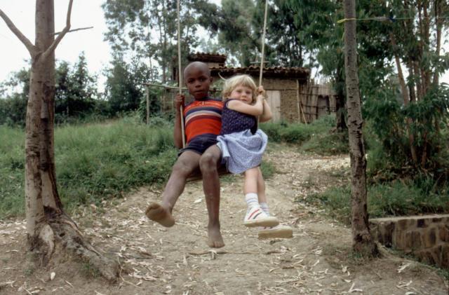 Due bambini di diversa razza giocano insieme in altalena