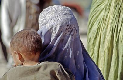 Una donna afgana, vestita con un burqa integrale, sorregge il proprio figlio all'interno del campo profughi Roghani a Chaman, una città al confine con il Pakistan