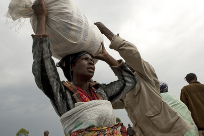 A woman resident of the Kibati camp of the Internally Displaced Persons (IDPs) carries a bag of food ration distributed by the World Food Programme in collaboration with the non-governmental organization, CARITAS.