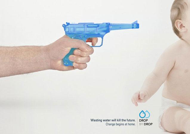 L'immagine raffigura una pistola ad acqua puntata alla testa di un neonato