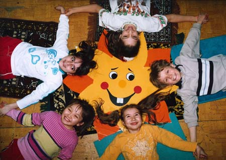 Receiving an education on intercultural dialogue in elementary school: five children play while holding hands and forming a star.