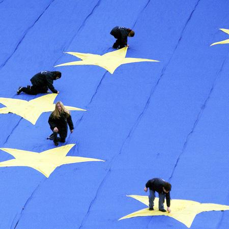 Particolare con quattro bambini appoggiati su 4 delle 12 stelle di una grande bandiera dell'Unione Europea