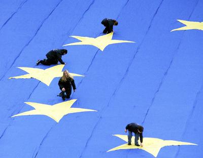 Particolare che ritrae quattro bambini appoggiati su 4 delle 12 stelle di una grande bandiera del Consiglio d'Europa.